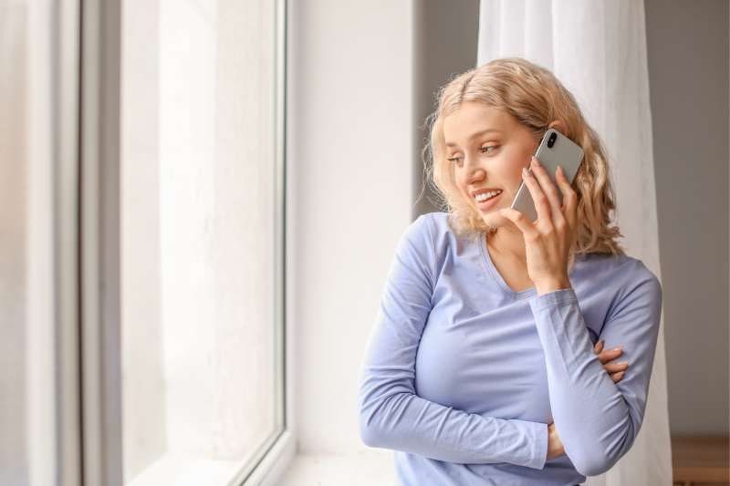 woman talking on phone inside home standing near the glass windows
