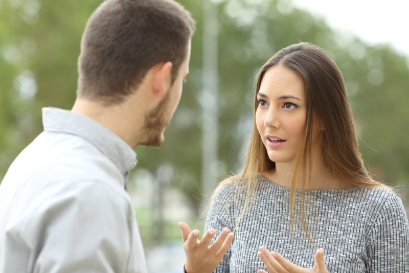 woman in gray sweater talking to man outdoor