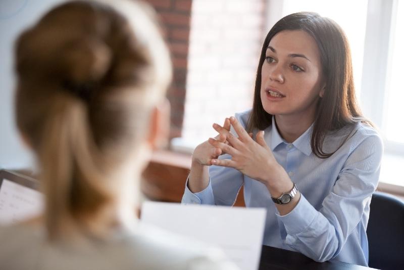 woman in blue shirt talking to woman