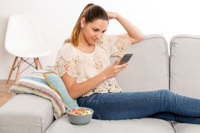 woman texting beside a food in a bowl in the sofa