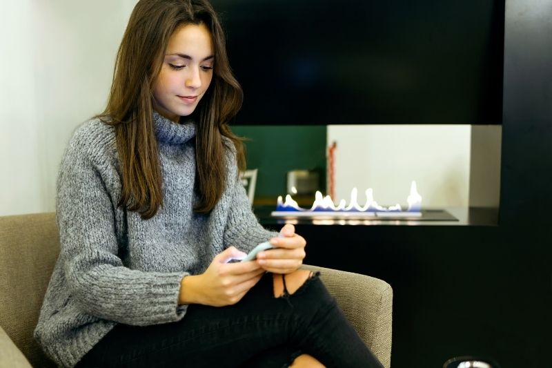 woman texting inside the house sitting on a couch wearing ripped jeans and a sweater