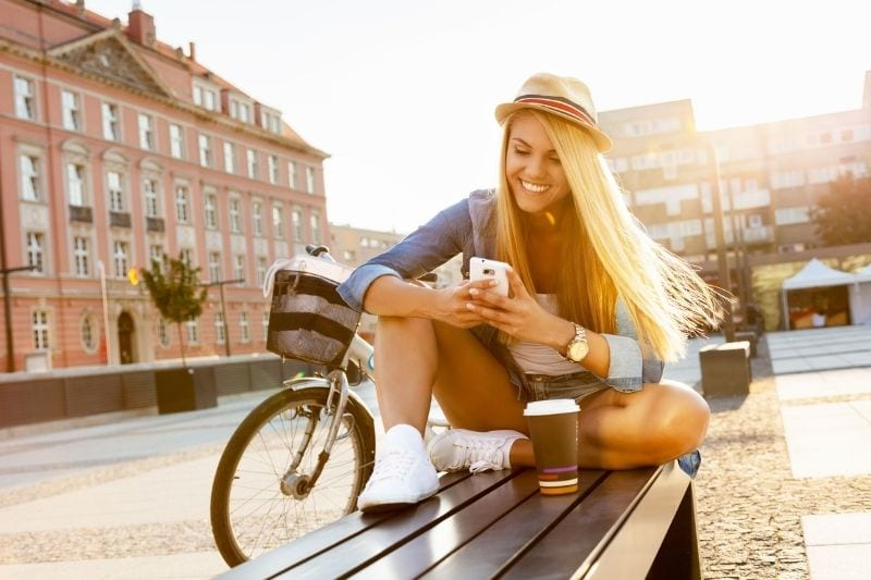 woman texting outdoors while sitting on a bench with coffee and a bicycle