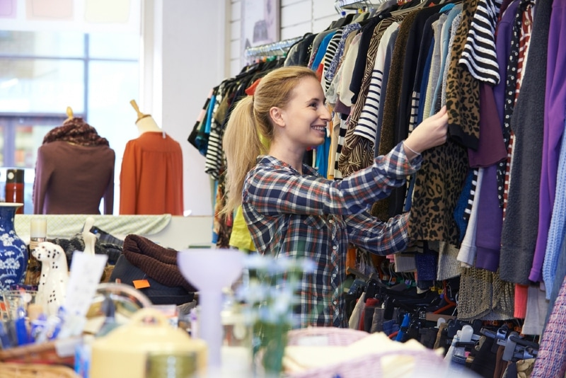 woman touching clothes in thrift shop