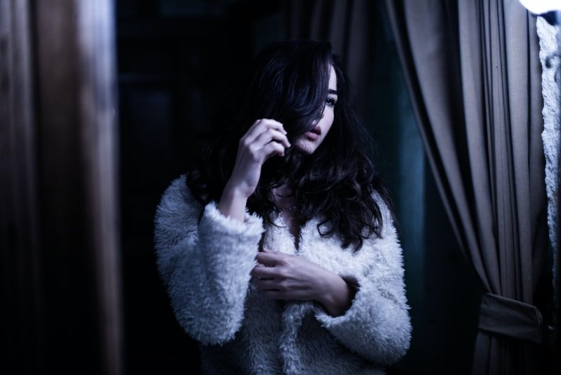 woman in white fur jacket touching her hair