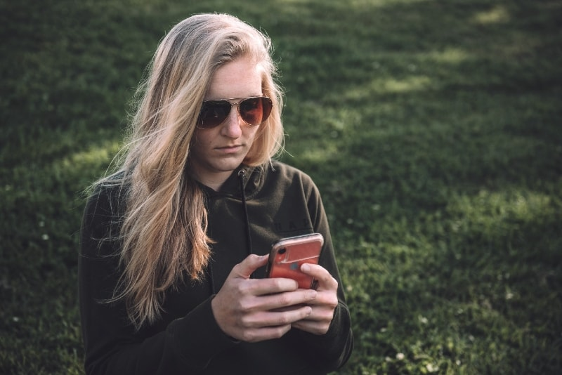 blonde woman using smartphone while sitting on grass