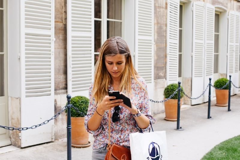 woman using smartphone while standing near building