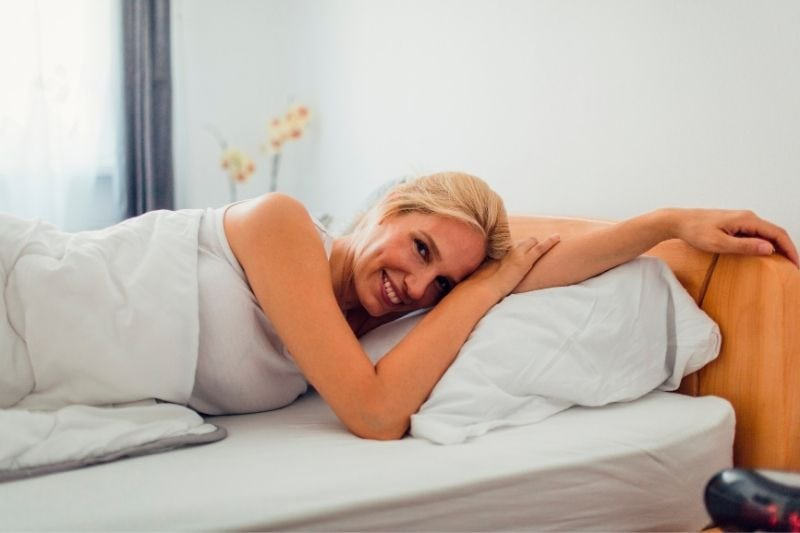 woman waking up in the morning from bed smiling