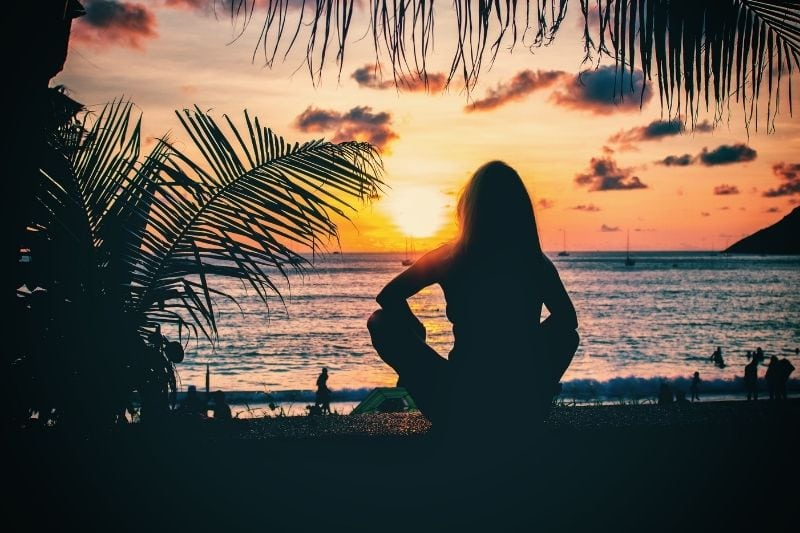 woman watching the sunset in Phuket Thailand near the beach while sitting