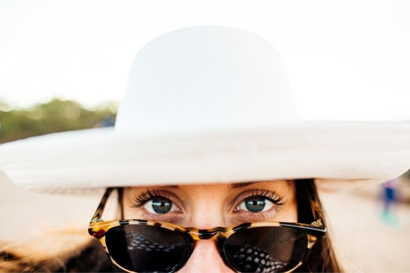 woman wearing hat and eyeglass showing the upper half of the face