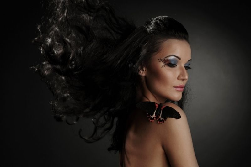 woman with black butterfly and her black hair float in the air