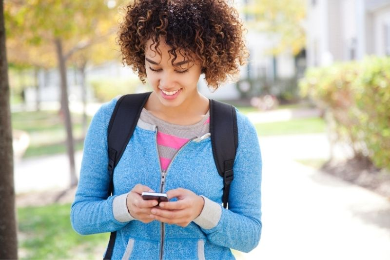 woman with curly hair with a backpack texting inside the university