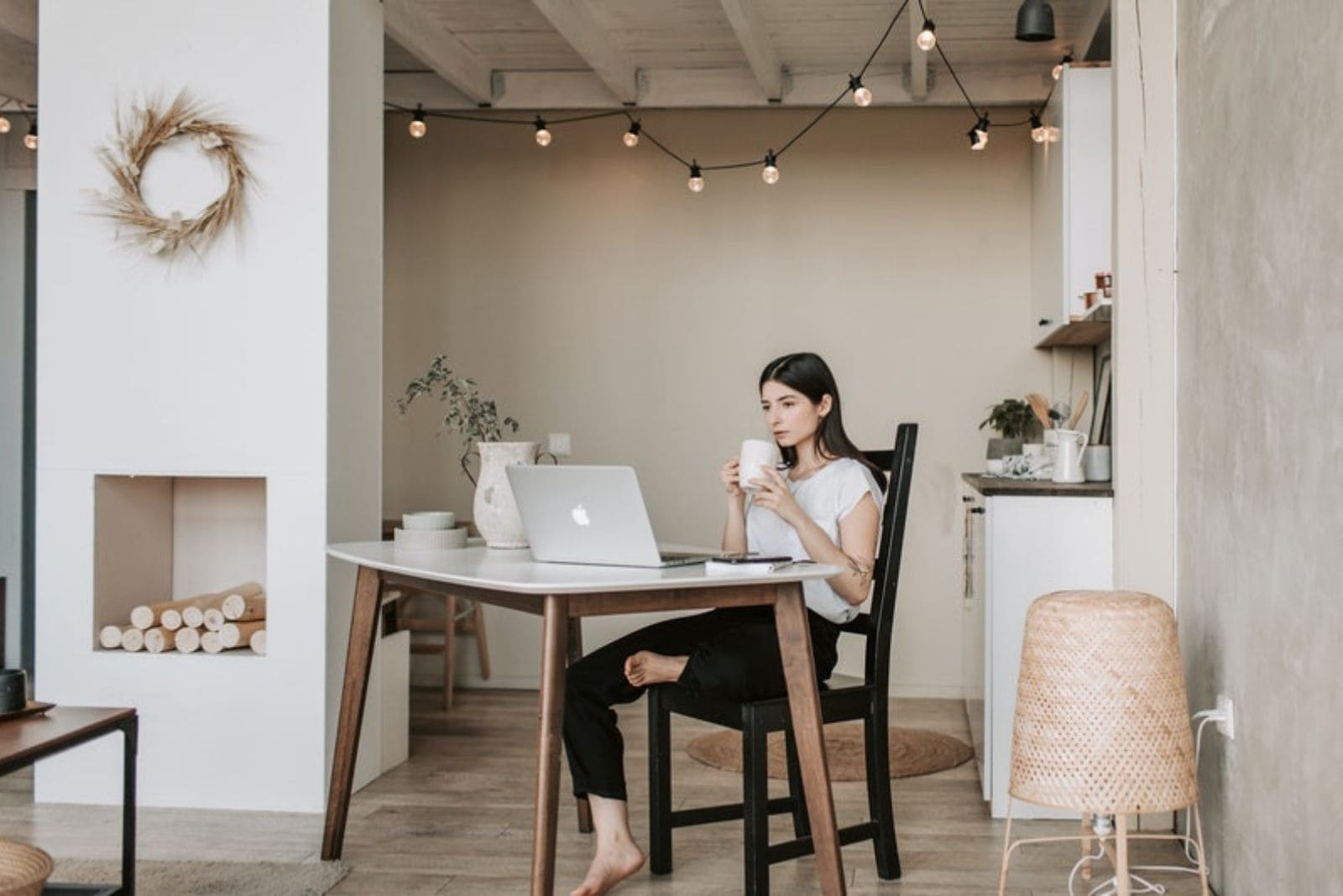 woman working at home drinking coffee with one foot rested on the chair