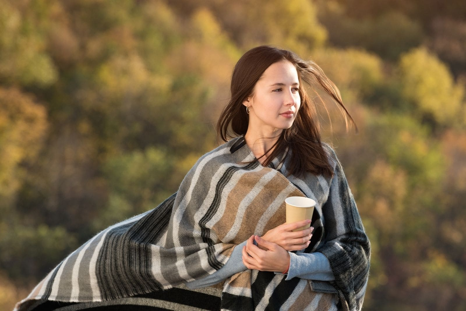 woman wrapped with blanket walking outdoors carrying coffee in paper cup