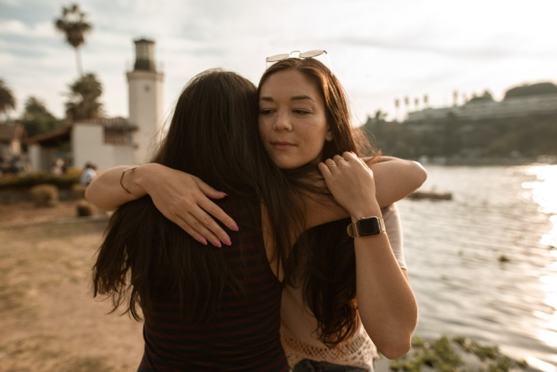 two women hugging while standing near water