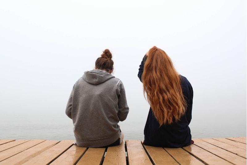 two women sitting on wooden dock near water