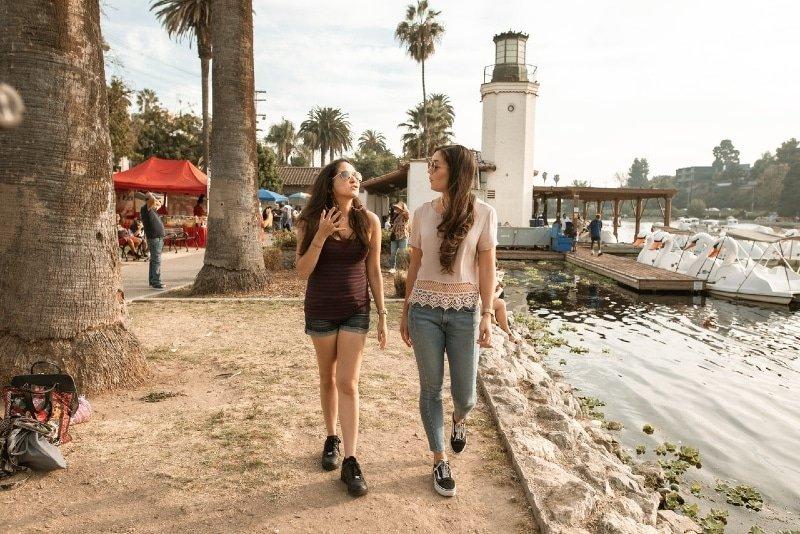 two women walking and talking near lake
