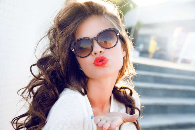 young attractive woman giving a kiss in air with red lips and an after salon hair
