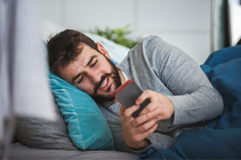 young bearded man lying in bed and texting