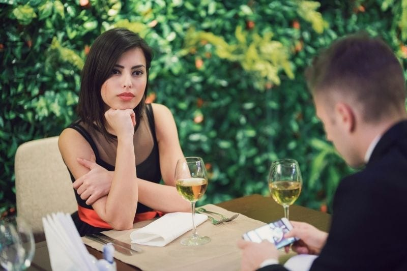 young businessman using smartphone during their date with a bored woman