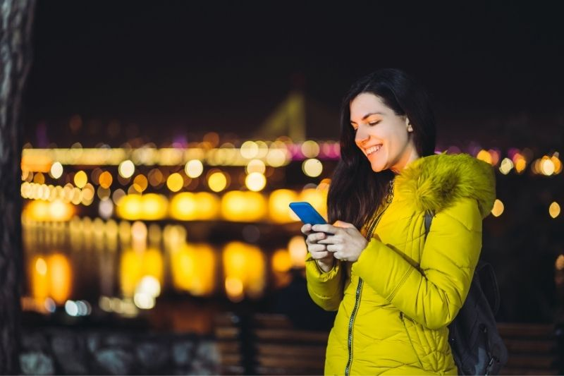 young caucasian woman texting outdoors in the night with city lights at the background
