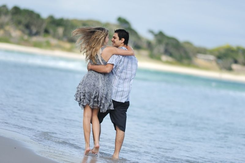 young couple at the beach hugging while taking a walk during a hot weather