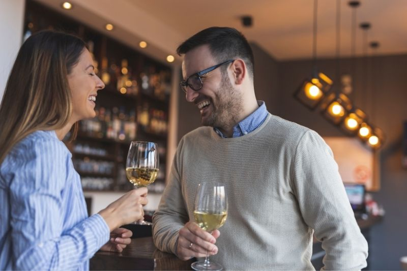 young couple dating standing near the counter drinking wine and laughing