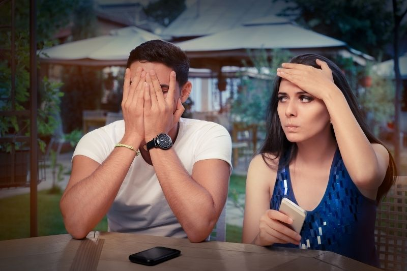 young couple having problem with their smartphones during while eating