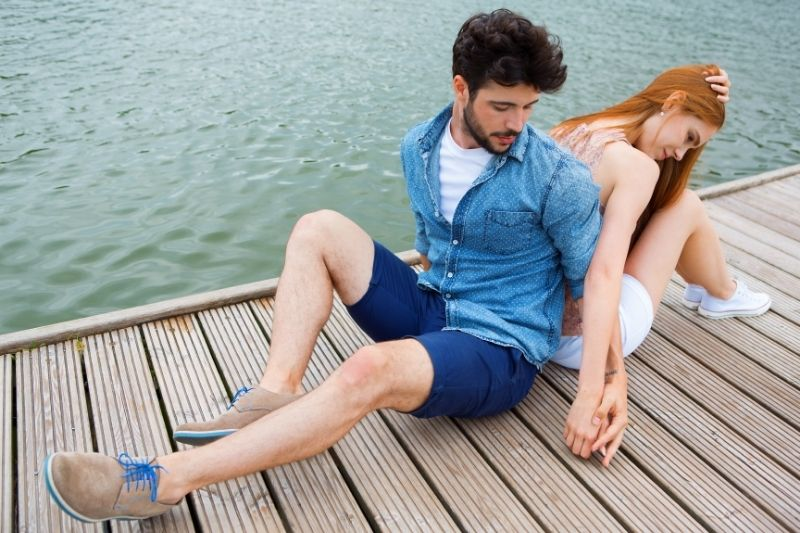 young couple on jetty sitting on the platform near the lake after an argument