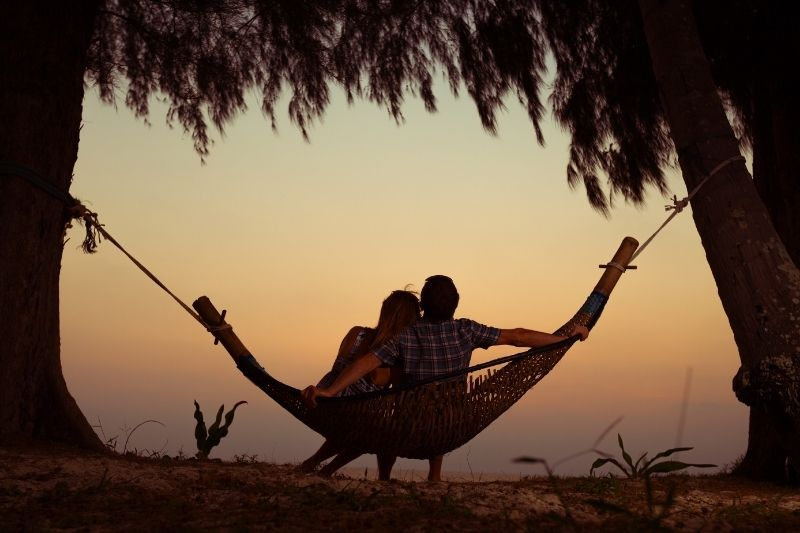young couple relaxing at the hammock under the tree during sunset