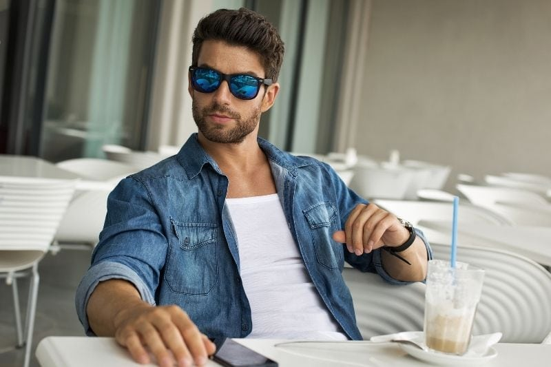 young handsome man in sunglasses sitting inside an empty cafe