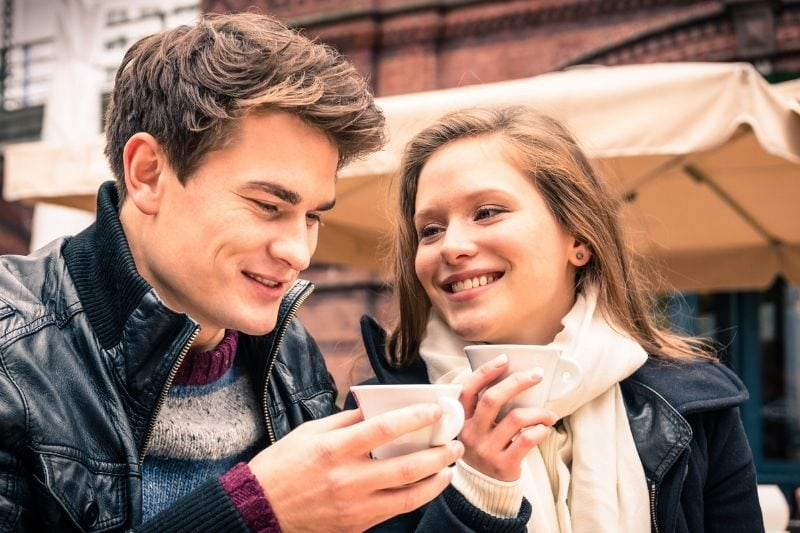 young lovely couple enjoying a cup of coffee outdoors