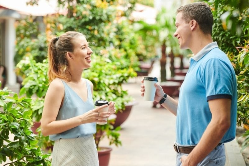 young man and woman talking in the walkway bringing cup of coffee while standing