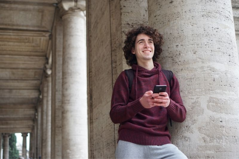 young man leaningon a circular column of a building texting and smiling while thinking