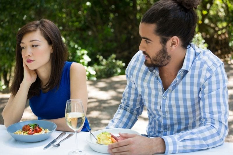 young man looking at the upset woman in an outdoor restaurant