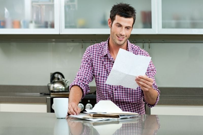 young man reading letter in the kitchen with papers in the countertop