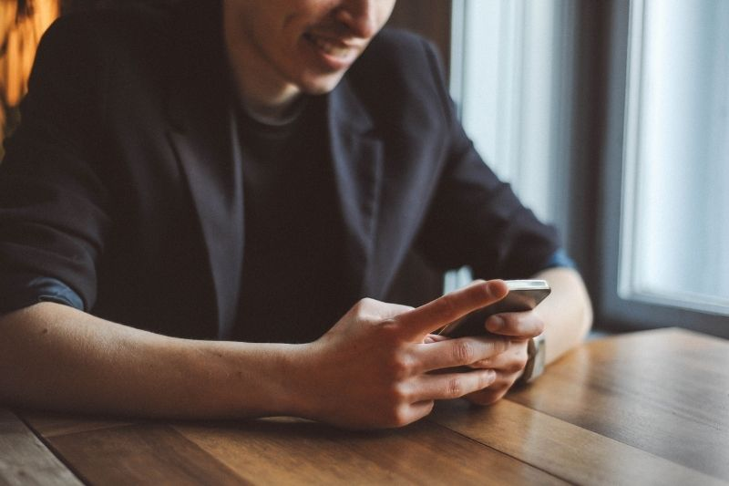 young man texting by the table in cropped image