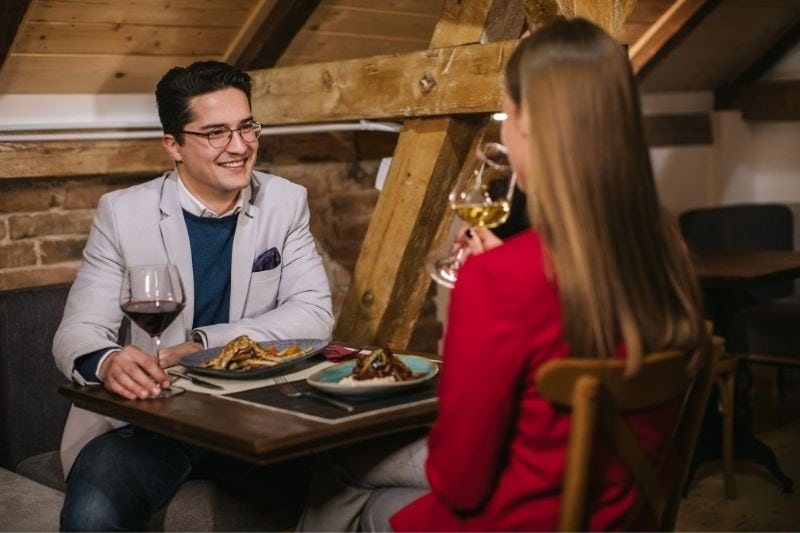 young modern couple on a first date eating dinner and having wine with the rear view of the woman