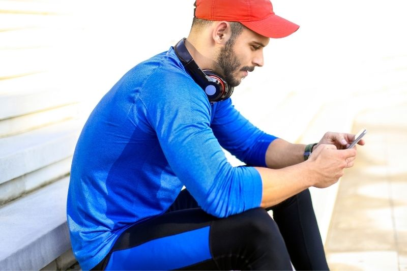 young smiling man wearing athletic wear and sitting in a bench texting