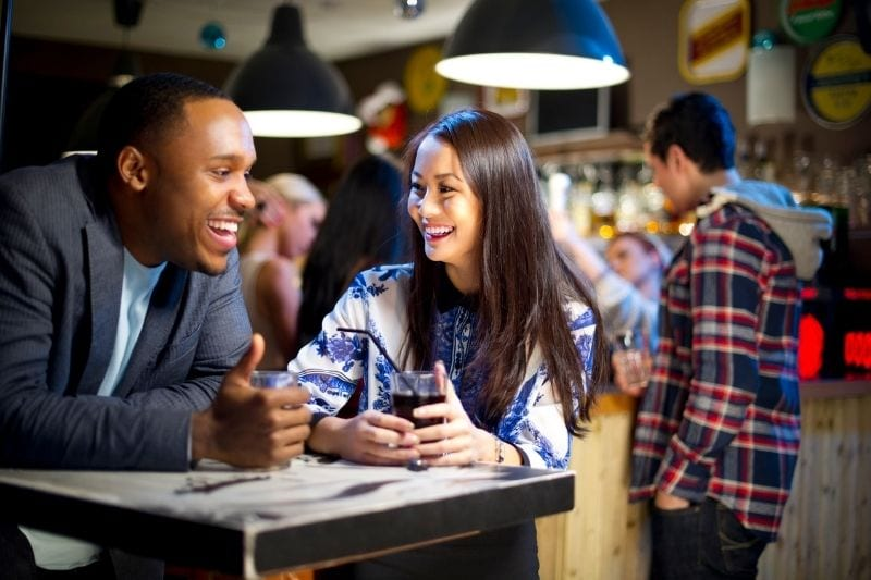 young woman chatting to a man in bar with a drink on their table