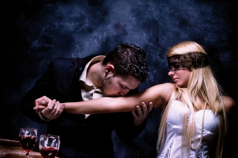 young woman covered her eyes with black lace with arms kissed by a man in suit