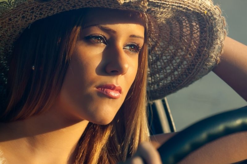 young woman driving a car wearing a hat