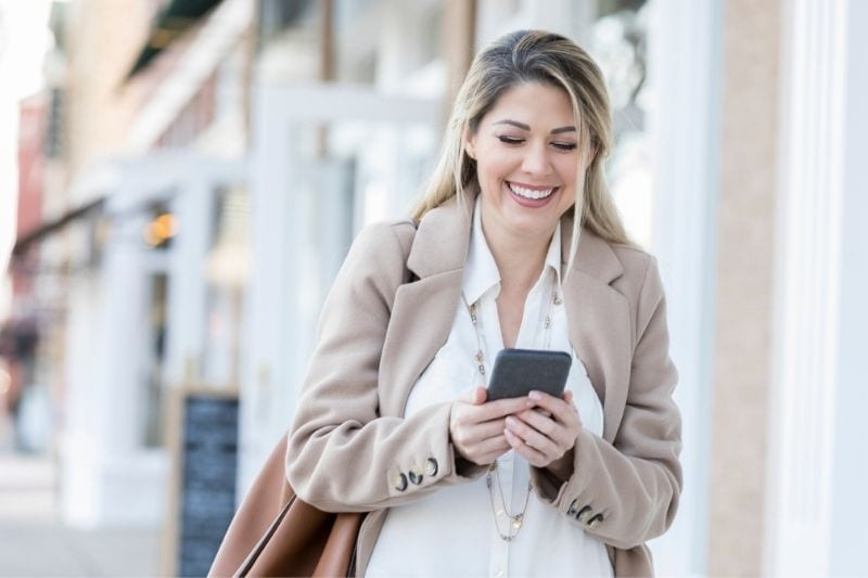 young woman laughs while reading the text message while walking outdoors