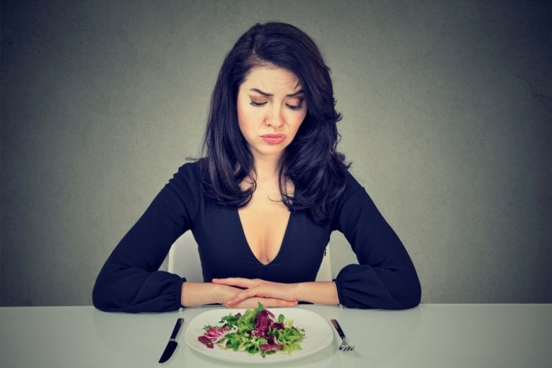 young woman looking at the plate with desperate expression
