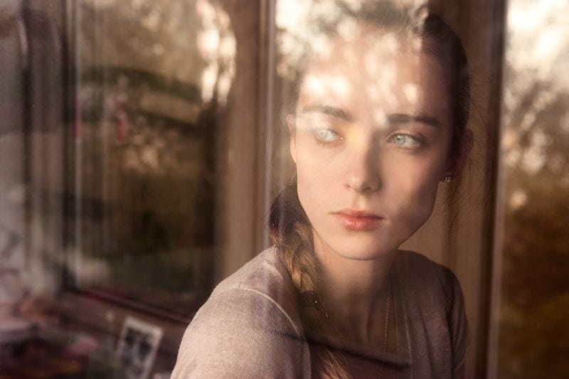 young woman looking thru the window with braided hair