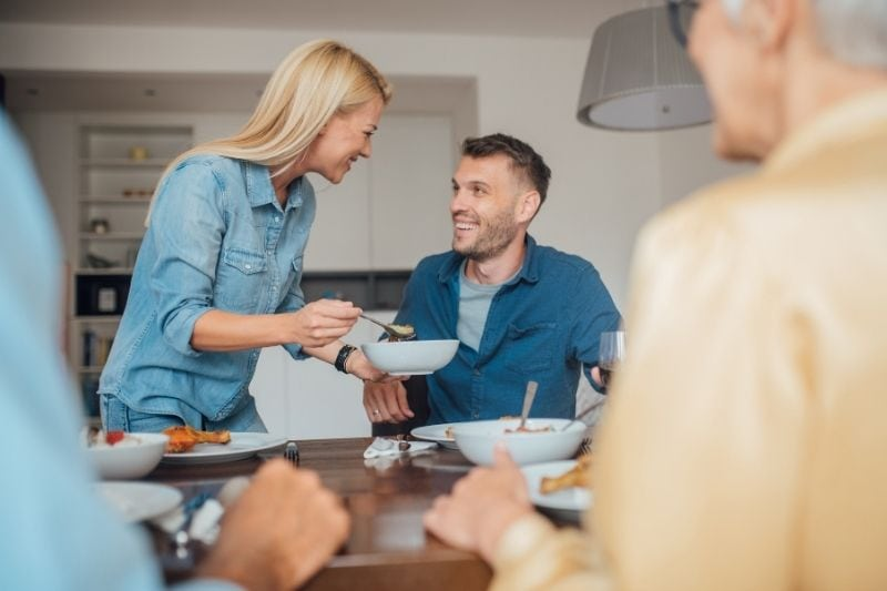 young woman serving food for her boyfriend during meal with old people joining the meal