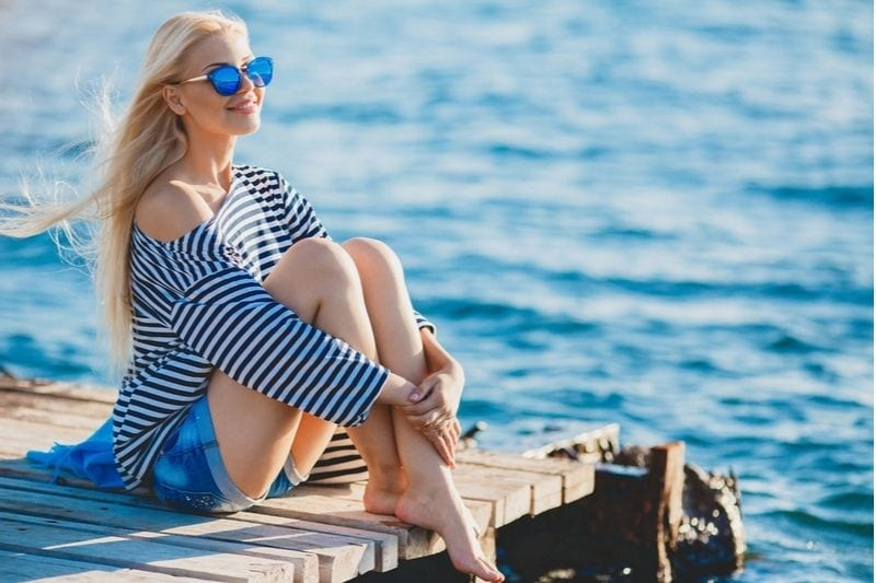 young woman sitting on the wooden platform near a body of water during summer