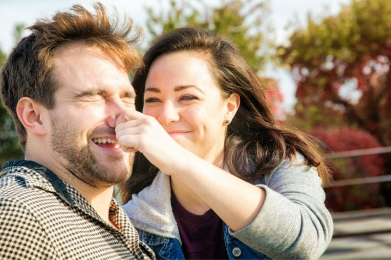 young woman teasing her boyfriend by pincing his nose