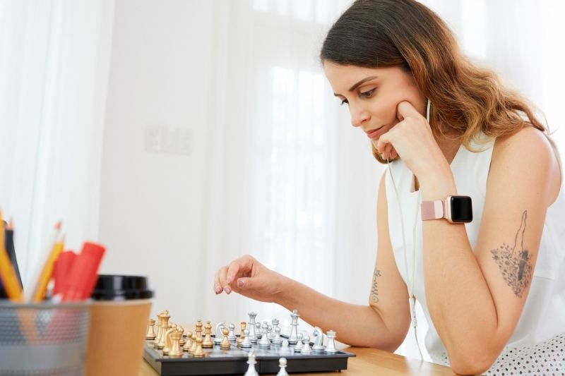 young woman thinking about the next move in chess playing at home
