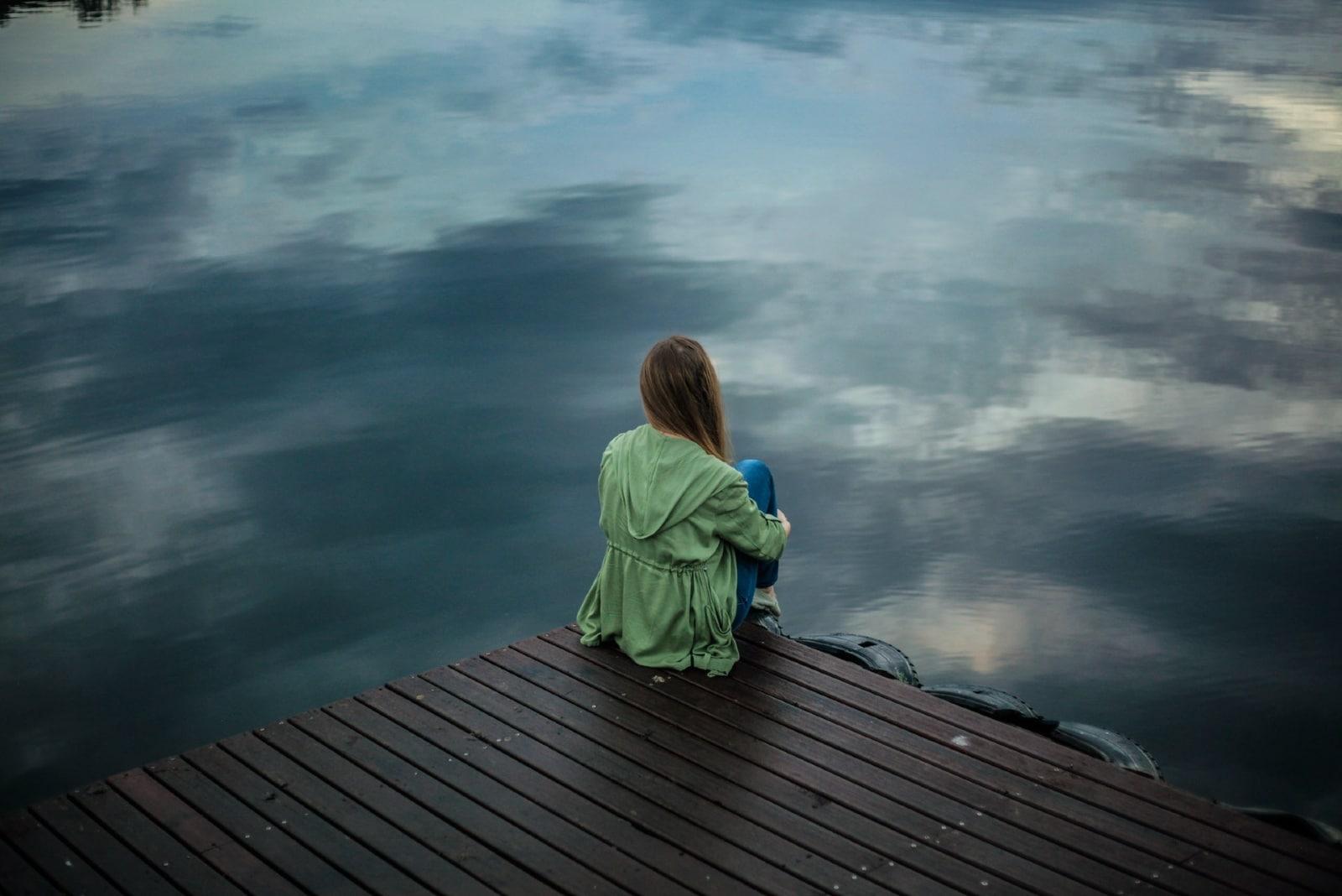 woman in green jacket sitting on dock