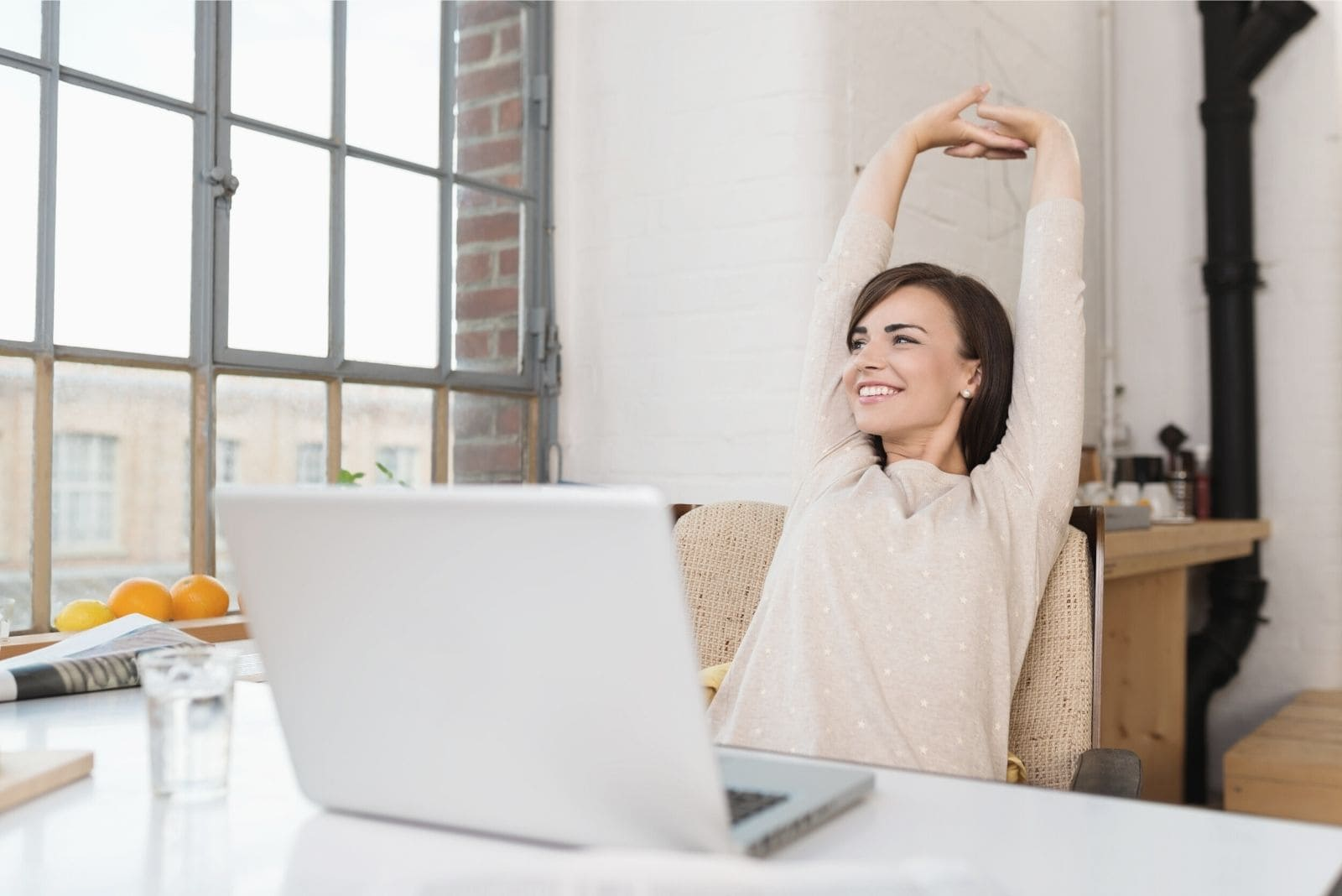 woman smiling and taking a break from office work while sitting by her office table and stretching her arms